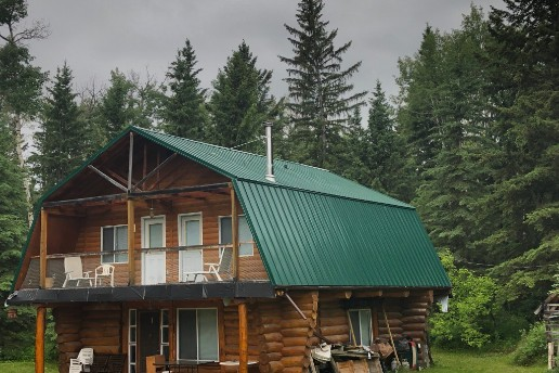 Cabin in rocky mountains with green metal roof