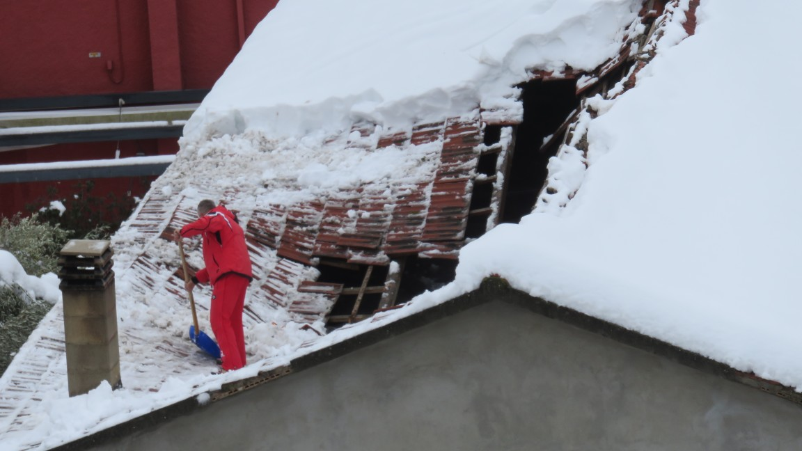 Collapsed roofman shovelling collapsed roof